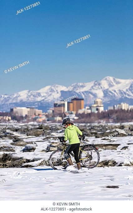 A Young Woman pushes her studded tire bicycle amongst the ice chunks in the Cook Inlet next to the Tony Knowles Coastal Trail, Anchorage, Southcentral Alaska