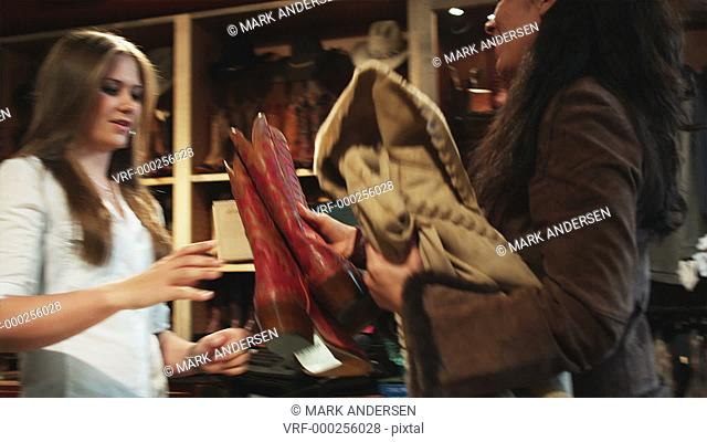 woman buying cowboy boots and a leather jacket at a western wear store