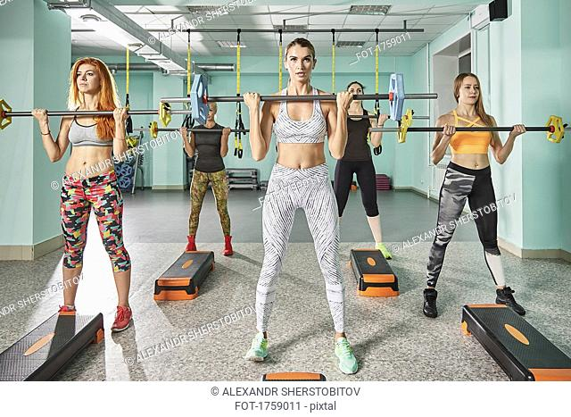 Full length of female trainer with determined young women picking up barbell during step aerobics