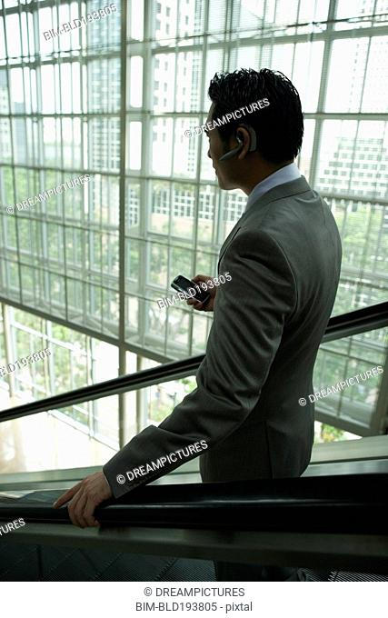 Chinese businessman holding cell phone on escalator