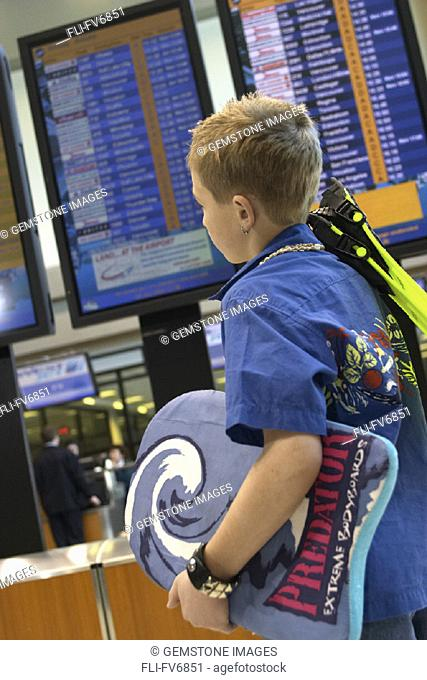 FV6851, Scott Dimond, Boy with Flippers and Body Board walking past Departure Board in Airport