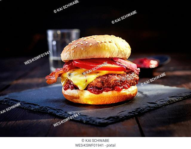 Cheeseburger with bacon on slate