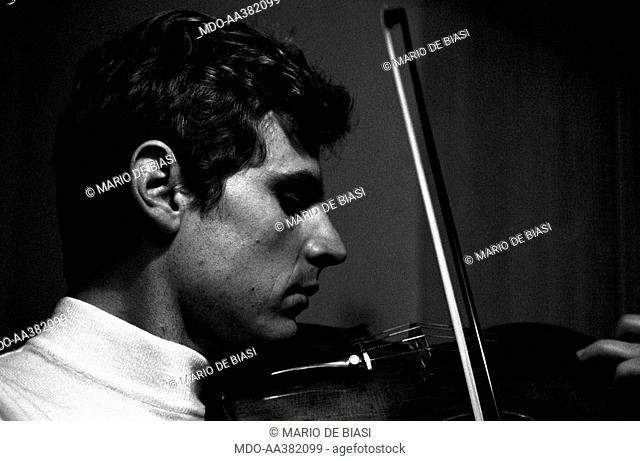 Uto Ughi playing. Italian violinist Uto Ughi (Diodato Emilio Ughi) playing the violin. Val Badia, January 1970