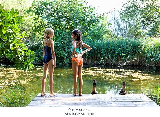 Two girls standing on jetty at a pond talking