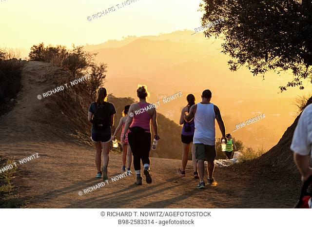 A small group of people walking on a hiking trail at sunset in the Hollywood Hills of Griffith Park, Los Angeles