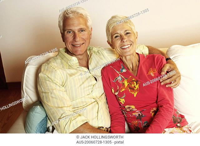 Portrait of a mature man and a senior woman sitting on a couch and smiling