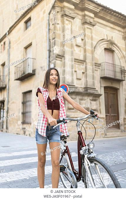 Spain, Ubeda, portrait of smiling young woman with bicycle crossing the street