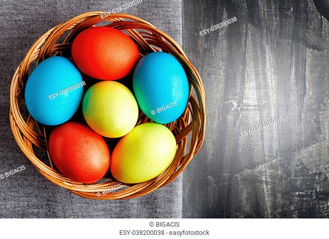 Easter eggs in a wicker basket, top view