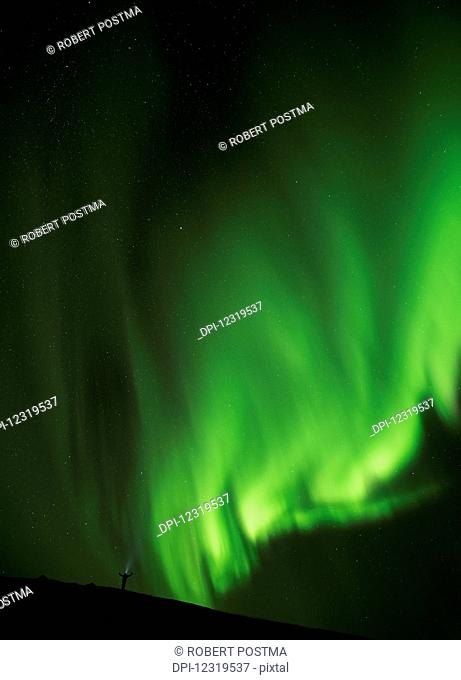 Man standing under a bright display of the northern lights; Iceland