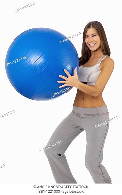 Attractive, fit woman holding exercise ball, smiling and looking at viewer