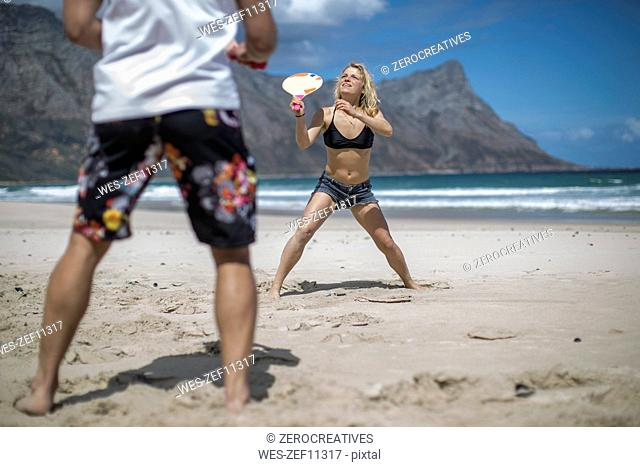 Young couple playing beach paddles on the beach