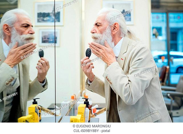 Senior businessman brushing beard in salon