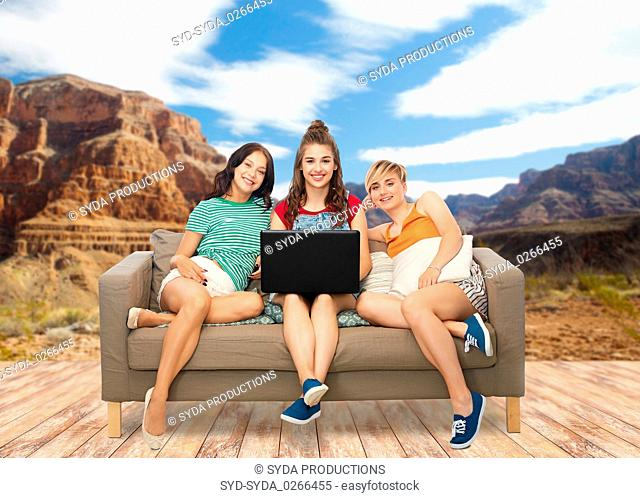 friends with laptop on sofa over grand canyon