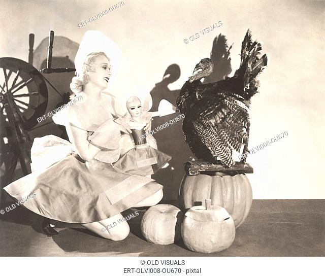 Woman holding doll wearing identical Thanksgiving costume