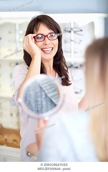 Woman at the optician trying on glasses
