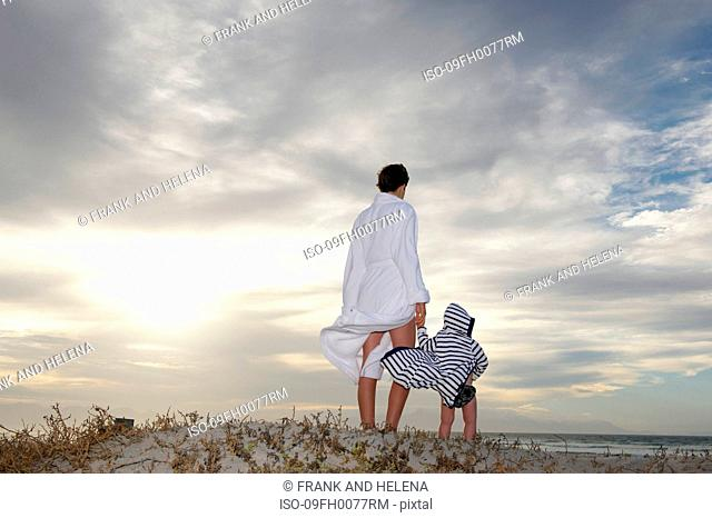 Woman and young boy looking out to sea