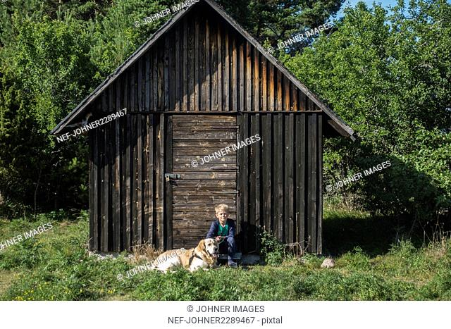 Boy with dog in front of wooden shed