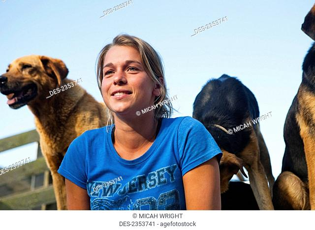 A Young Woman With Sheep Dogs At Blue Duck Lodge, In The Whanganui National Park; Whanganui, New Zealand