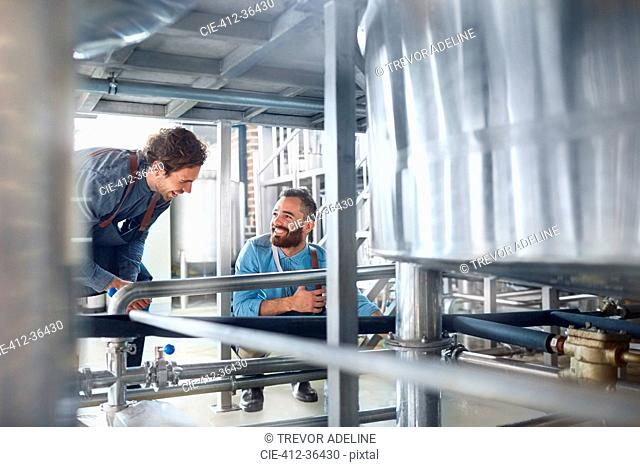 Male brewers talking vat in brewery