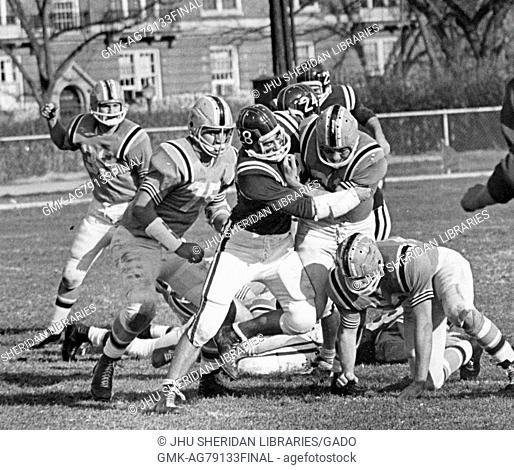 A Johns Hopkins University football player with the football getting tackled by a player on the opposing team with players from both teams in motion in the...