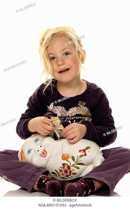 Child with piggy bank saving banknotes