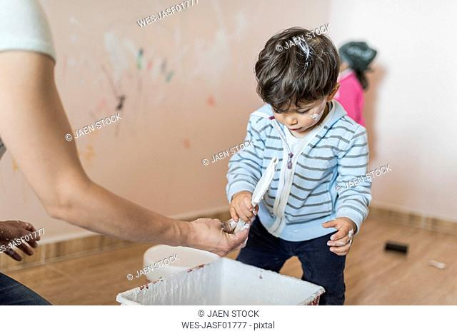 Mother and children painting wall at home