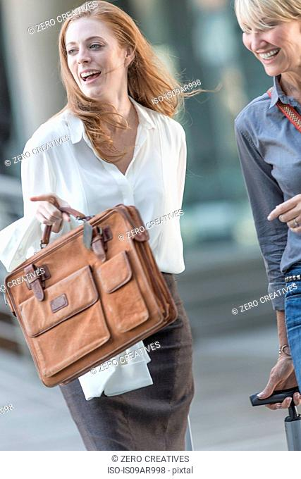 Two businesswomen leaving hotel in a hurry