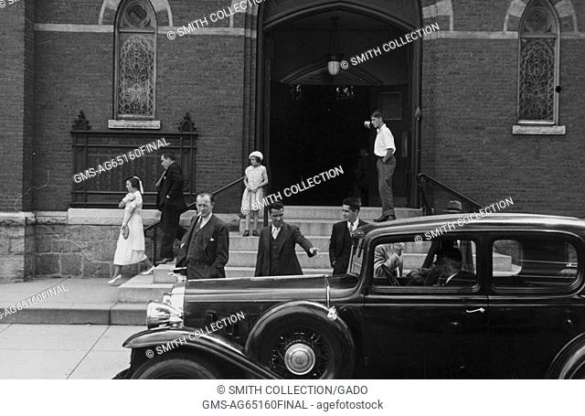 Small gathering of people outside of a church, car with two men parked in front, men in three piece suits next to the car