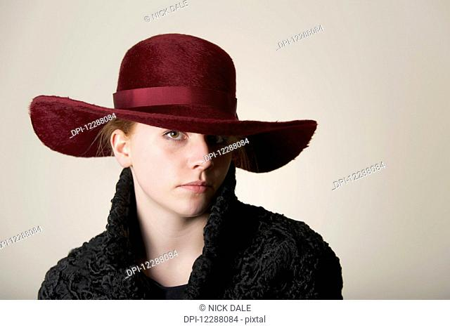 Young woman with red hair in maroon hat and black coat; Caldecott, England
