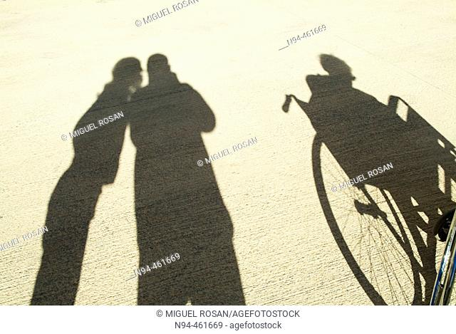 Shadow on the floor of an old woman in a wheelchair, accompanied by her son and granddaughter