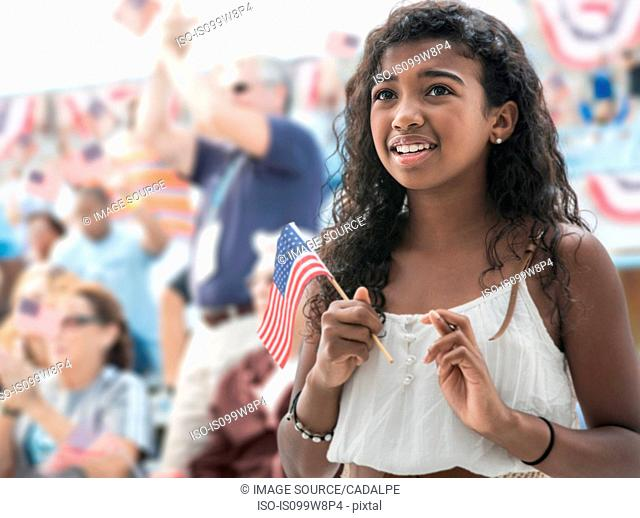 Girl holding american flag, crossing fingers