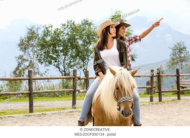 Young women riding on a horse at riding stable