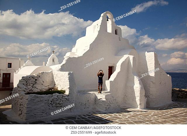 Tourist taking photos in front of the Church of Paraportiani, Mykonos, Cyclades Islands, Greek Islands, Greece, Europe