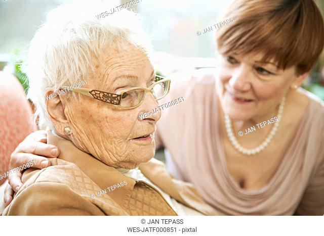 Portrait of senior woman with Alzheimer's disease with her adult daughter watching in the background