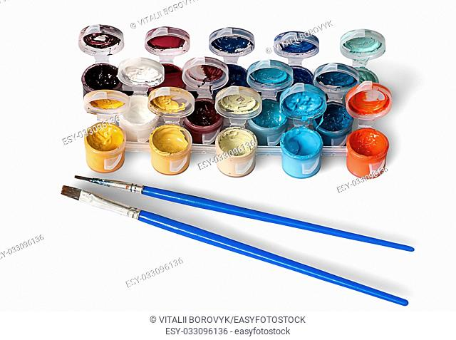 Set of colorful acrylic paints in jars and two brushes isolated on white background