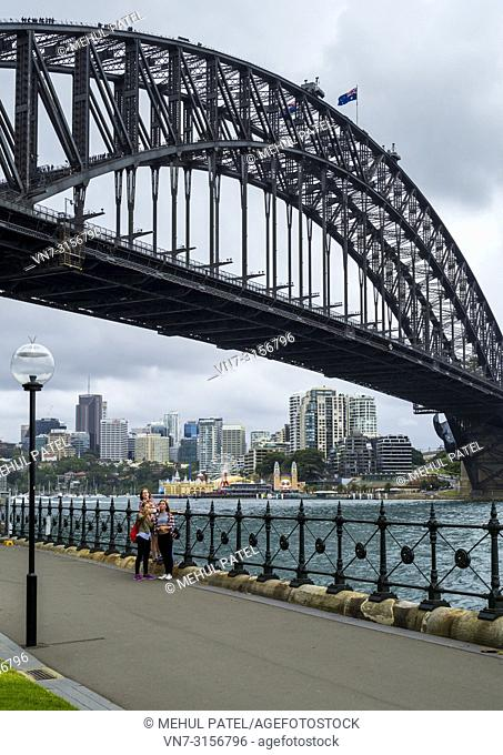 Children taking a selfie on promenade underneath Sydney Harbour Bridge, Sydney, New South Wales, Australia
