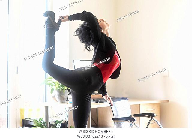 Young dancer stretching in office