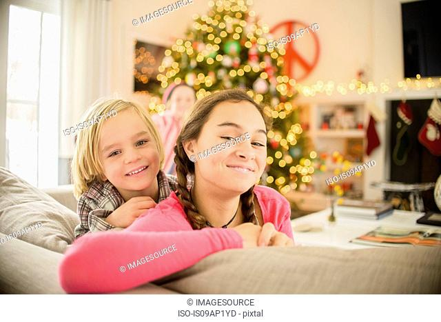 Portrait of teenage girl and brother leaning on sofa at christmas