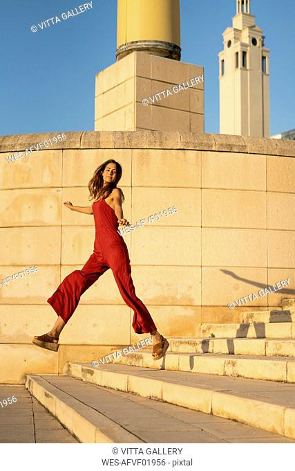 Spain, Barcelona, Montjuic, young woman wearing red jumpsuit jumping on stairs