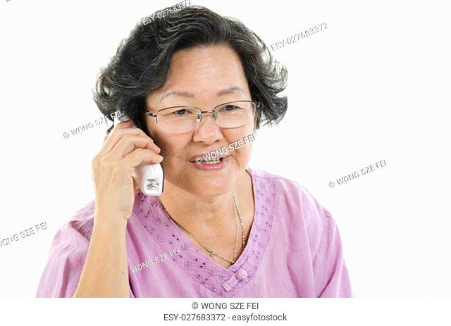 Portrait of 60s Asian senior adult woman calling on phone, isolated on white background