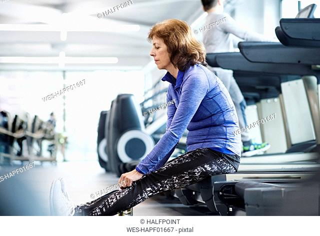 Senior woman resting after working out in gym