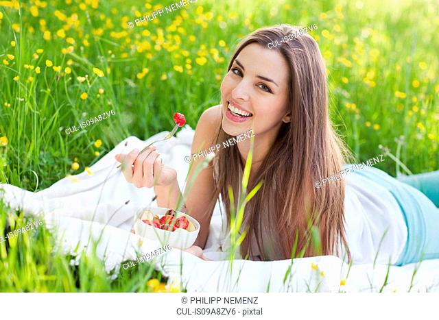 Young woman in field of buttercups eating strawberries