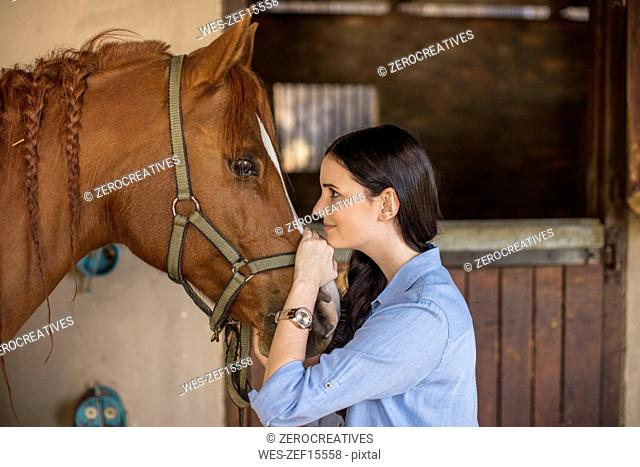 Smiling woman caring for a horse on a farm
