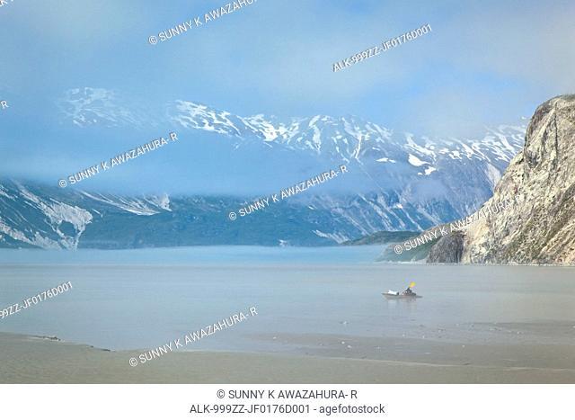 A kayaker paddles through the mist in Muir Inlet, Glacier Bay National Park & Preserve, Southeast Alaska, Summer