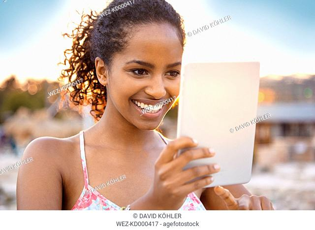 Happy young woman with digital tablet at sunset