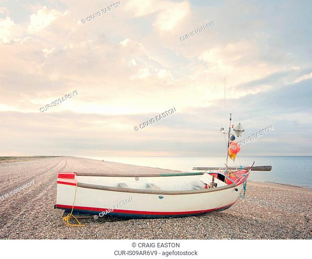 Fishing boat on empty shingle beach, Norfolk, England, UK