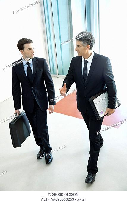 Businessmen passing through office building lobby together