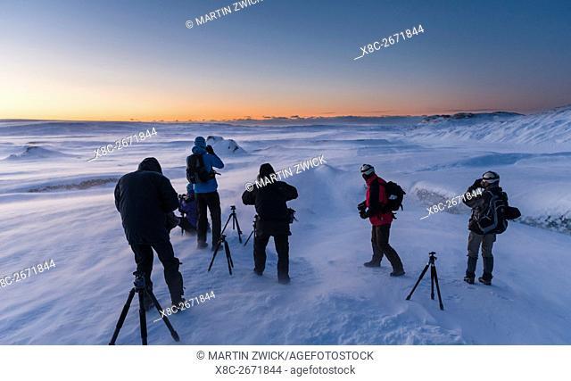 Photographers at sunrise and in a winter storm on the glacier Breithamerkurjoekull in the Vatnajoekull NP . europe, northern europe, iceland, February