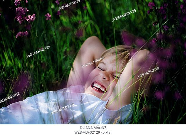 Laughing little boy lying on meadow in the garden