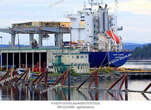 Cargo ship loading paper prodcuts from Catalyst Paper's pulp mill, Crofton, Vancouver Island, British Columbia